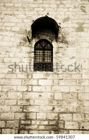 Lonely prison window on a high wall - stock photo