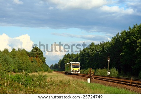 Lonely rail bus passing the forest with colorful sky over