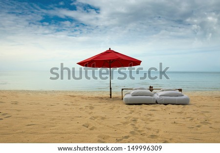Lonely red umbrella at the tropical beach - stock photo