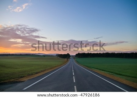 lonely road at sunrise - stock photo