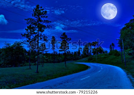 Lonely road in the country illuminated by a bright full moon at midnight - stock photo