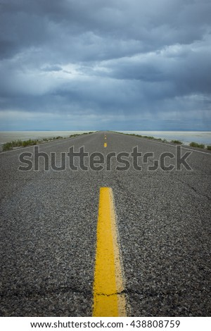 Lonely road one point perspective highway yellow stripes against blue gray storm horizon travel trip vertical  - stock photo