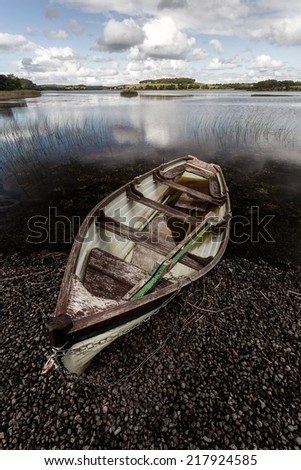Lonely rowing boat at lake in ireland - stock photo
