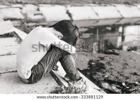 lonely sad boy. lonely sad boy dropped his head on his chest and weeping hid his face - stock photo