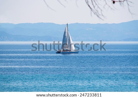 Lonely sailboat on the big blue sea - stock photo