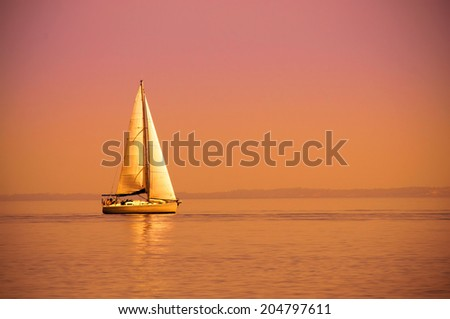Lonely sailboat on the sea at sunset - stock photo