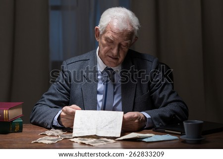 Lonely senior businessman spending night at the office - stock photo