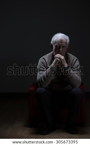 Lonely senior man sitting in a armchair - stock photo