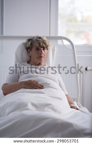 Lonely senior sick woman left in hospice - stock photo