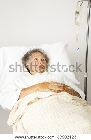 Lonely senior woman in the hospital bed, hooked up to an IV. - stock photo