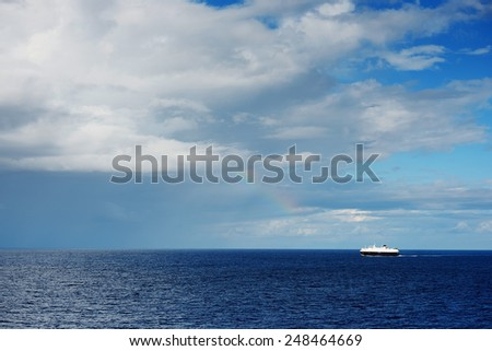 Lonely ship in front of stomy ocean clouds  - stock photo