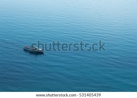 Lonely ship sails on the blue boundless sea at sunny day, top view