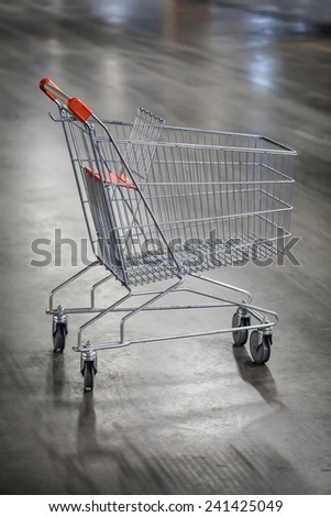 Lonely shopping cart in parking lot of a shopping mall. - stock photo