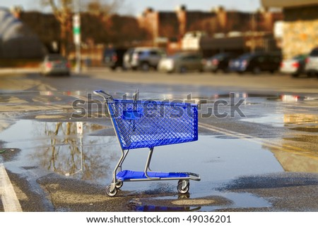 Lonely shopping cart on the shopping mall parking lot with sky reflection. - stock photo