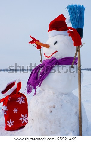 Lonely snowman with Santa's hat at a snowy field at winter time - stock photo