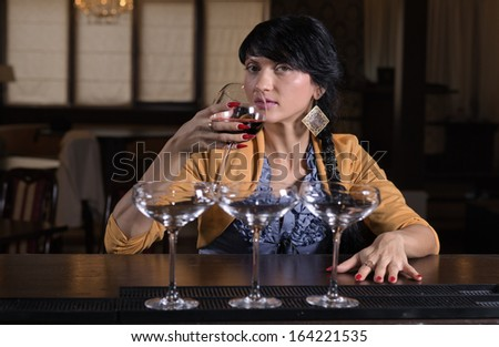 Lonely stylish young woman sitting drinking alone at a bar in a hotel or nightclub, view with three cocktail glasses in the foreground - stock photo