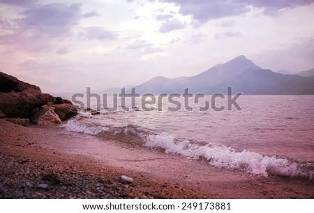 lonely sunset beach at garda lake, italian landscape - stock photo
