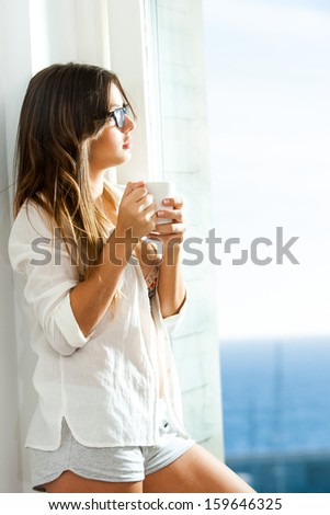 Lonely teen girl standing next to window with coffee mug. - stock photo
