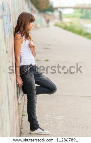 Lonely teenage girl leaning against concrete wall in urban environment. - stock photo