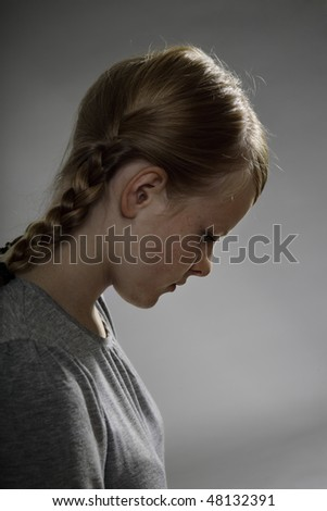 Lonely teenage girl on gray background - stock photo