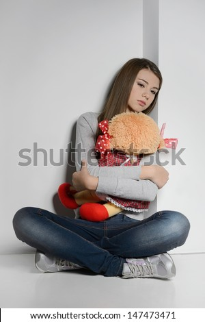 Lonely teenage girl. Sad teenage girl sitting on the floor and hugging a toy - stock photo
