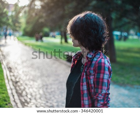 Lonely teenage girl standing in a park  - stock photo