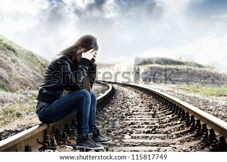 Lonely teenage girl with hands over her face sitting on the railroad - stock photo
