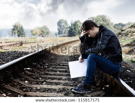 Lonely teenage girl with letter sitting on the railroad. - stock photo