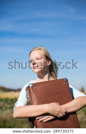 Lonely teenage girl with loose blond hair holding old suitcase on rural background looking away copyspace - stock photo