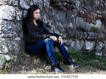 Lonely teenager looking off into the distance, sad expression face, leaning on stone wall. - stock photo