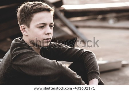 Lonely teenager sitting on roof the house - stock photo