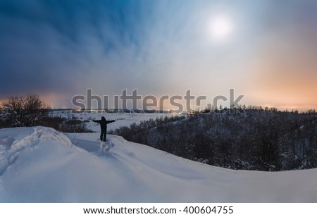 Lonely traveler is standing on the hill in the moonlight and looking at the night landscape. The man was lost in contemplation. He is enjoying the beautiful night view. - stock photo