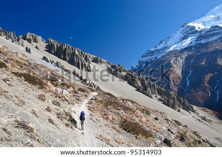 Lonely trekker on the trail in Nepal mountains - stock photo
