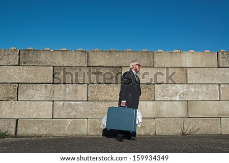 Lonely wandering depressed senior business man with sunglasses without a job and homeless on the street. Holding a suitcase. Wearing a dirty suit. - stock photo