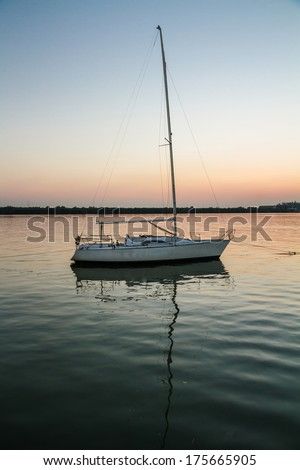 Lonely white sailboat in twilight time - stock photo