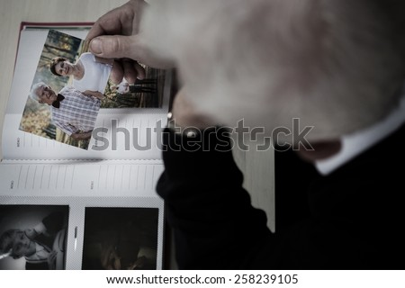 Lonely windowed man watching photo album and recollecting - stock photo