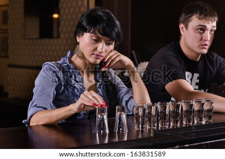 Lonely woman alcoholic sitting at a bar counter with a long line of full shot glasses staring morosely at the counter as she drinks her way through them - stock photo