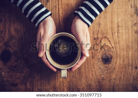 Lonely woman drinking coffee in the morning, top view of female hands holding cup of hot beverage on wooden desk, retro toned. - stock photo