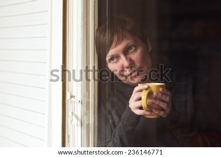 Lonely woman drinking cup of coffee by the window of her living room, looking out with a sad look on her face. Selective focus with shallow depth of field, shot through the window. - stock photo
