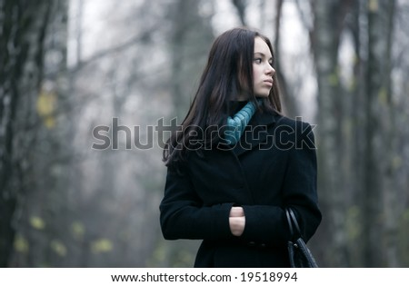 Lonely woman in a forest. Autumn november season. - stock photo