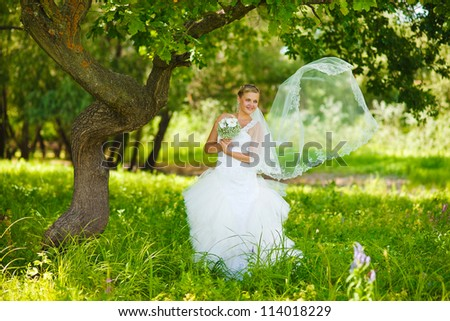 lonely woman in a white dress at a wedding the bride is the tree in a green forest she develops veil