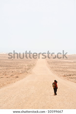 Lonely woman is walking on the desert road - stock photo