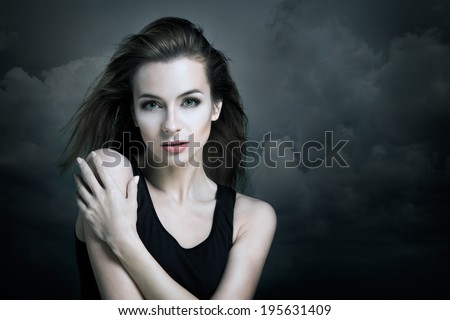 Lonely Woman on the Background of Dark Moody Sky. Sadness Concept.  - stock photo