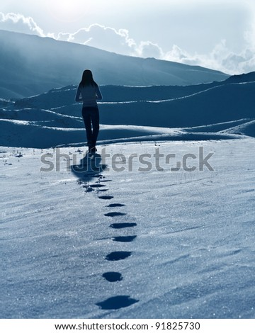 Lonely woman silhouette at winter mountains, footprints on the snow, enjoying wintertime nature view,one girl walking outdoor - stock photo