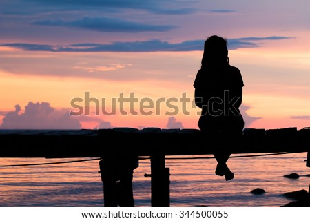 Lonely woman sitting on a wooden bridge sunset.are Lonely. style abstract shadows.silhouette - stock photo