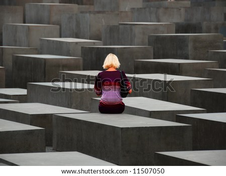 Lonely woman sitting on Berlin Holocaust Monument stone - stock photo