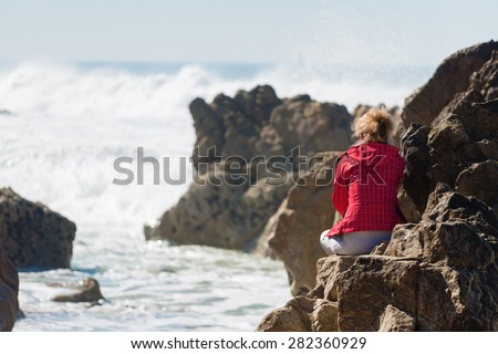 Lonely woman sitting on rock , looking at ocean.Unrecognizable person, copy space - stock photo