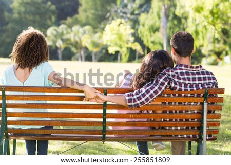 Lonely woman sitting with couple in park on a sunny day - stock photo