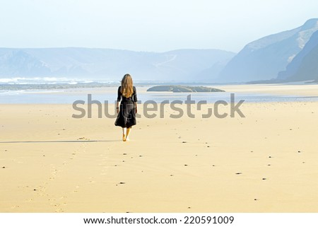Lonely woman walking at the beach - stock photo