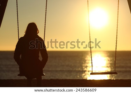 Lonely woman watching sunset alone in winter on the beach at sunset - stock photo